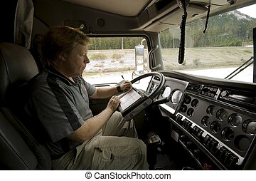Trucker updating his logbook - A Truck Driver updates his...
