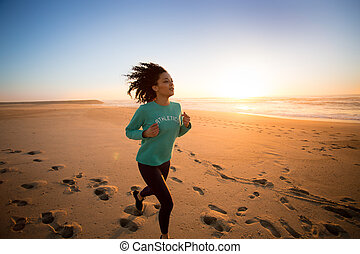 Afro woman running - Young afro woman running on the beach