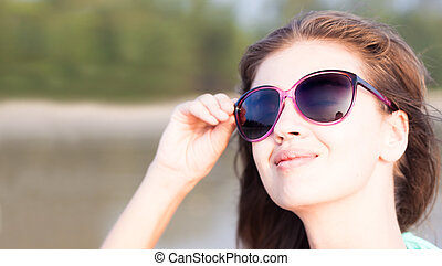 Portrait of young woman in pink sunglasses smiling on beach