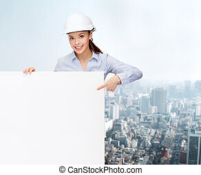 businesswoman in helmet pointing finger to board - building,...