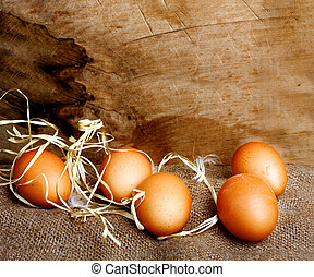 Fresh chicken eggs in straw nest on wooden wall background