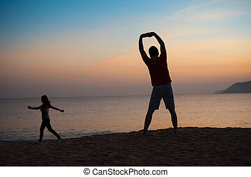 Silhouette of runner on the beach at sunset - Silhouette of...