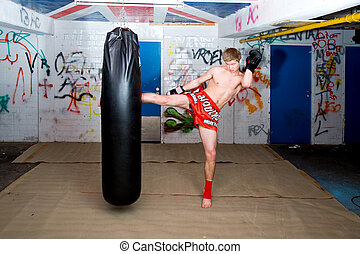 High Kick - A muay thai fighter giving a high kick during a...
