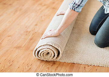 close up of male hands unrolling carpet - repair, building...