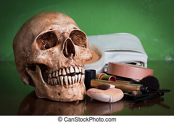 Weathered human skull with makeup brush and cosmetics.
