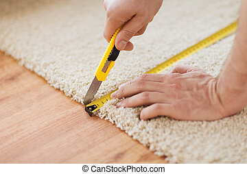 close up of male hands cutting carpet - repair, building and...