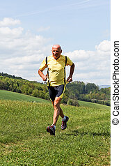 Older man jogging running on meadow - Older Senior running...