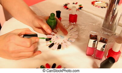 Nail technician painting fake nails - Nail technician...