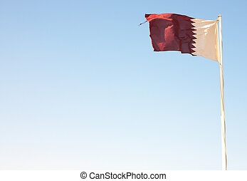 National flag of Qatar waving against a blue desert sky...