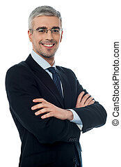 Smiling senior businessman with arms crossed - Smiling...