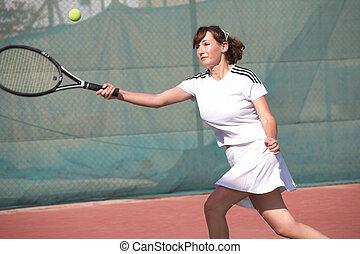 Female Tennis Players - Young women playing tennis in the...