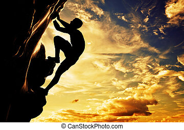 A silhouette of man free climbing on rock, mountain at...