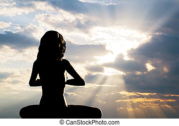 A silhouette of a woman sitting in yoga position, meditating...