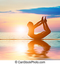 A silhouette of a woman in bow yoga position, meditating...
