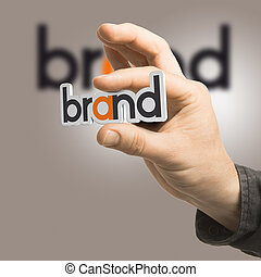 Brand - Company Identity - One hand holding the word brand...