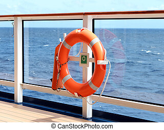 Lifesaver - An orange lifesaver on the deck of a cruise ship