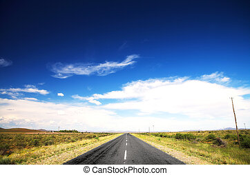 Road and blue sky - Long straight road under a dramatic dark...