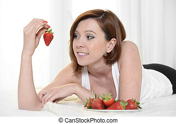 Young Attractive woman eating a bowl of strawberries in bed