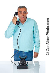Scared man while talking with bakelite telephone.