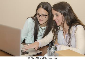 Two beautiful women using a computer - Young women using a...