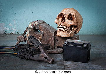 Group of objects on table. human skull, bench vise, jumper...