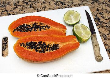 Papaya and Lime - One large dark orange papaya fruit cut in...