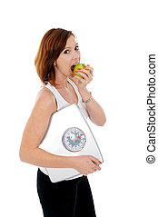 young attractive woman with apple and bathroom scale - young...