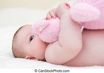 Baby girl - Infant baby girl playing on a white blanket.