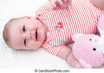 Baby girl - Infant baby girl playing on a white blanket
