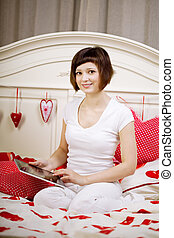 Woman with a tablet computer on the bed