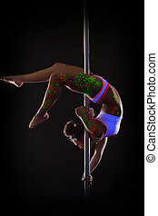 Attractive girl dancing on pole upside down