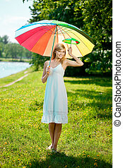 Smiling woman with a rainbow umbrella outdoors