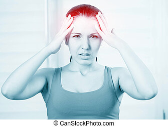 woman with a headache - young woman with a headache holding...