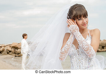 Young and beautiful bride and groom on the beach