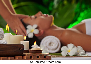 massage. focused on candles - portrait of young beautiful...