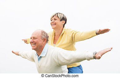 Happy man giving piggyback to woman - Couple piggyback...