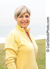 Beautiful aged woman in the park - Smiling middle aged woman...