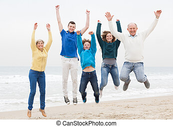 Happy family have fun at vacation - Happy family jumping on...