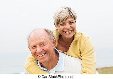 Mature man giving woman piggyback