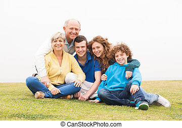 Happy family posing together - Happy family sitting on lawn...