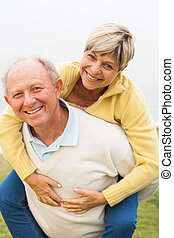 Mature couple having fun - Aged man giving piggyback ride