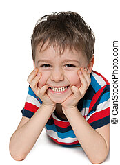 Laughing preschool boy is lying on the white background