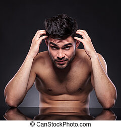 naked young man scratches head - naked young man sitting at...