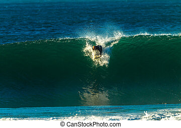 Surfer Ocean Waves - A surfer riding ocean waves that crash...