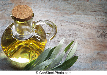 Olive Oil and Olive Leaves on Rustic Timber - Bottle of...