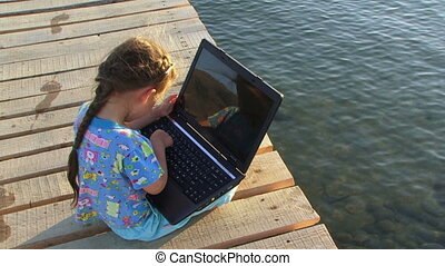 Child plays with notebook sitting on dock - A little girl is...