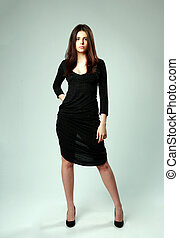 Young beautiful woman in black dress standing on gray background