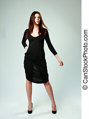 Young beautiful woman in black dress standing on gray...