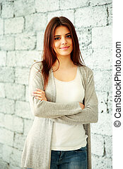 Young smiling woman with arms folded standing near brick wall