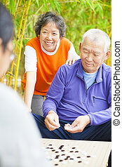 seniors play weiqi with friends in the park